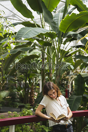 young woman in greenhouse reading book