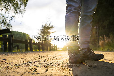 man standing in street at sunset