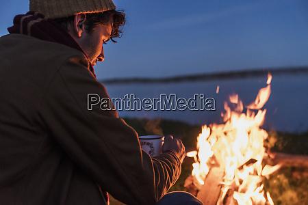 young man sitting at a campfire