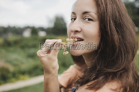 portrait of woman eating white currants