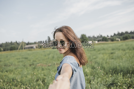 smiling woman wearing sunglasses holding hand