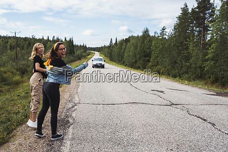 finland lapland two happy women hitchhiking