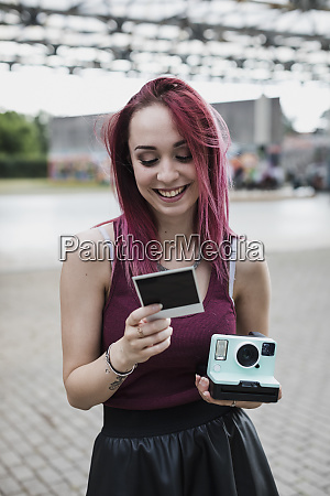happy young woman with instant camera