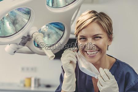 dental surgeon removing surgical mask portrait