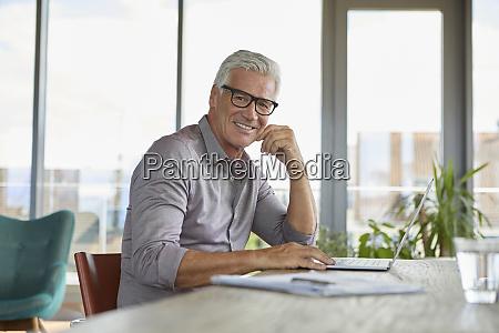 portrait of smiling mature man using