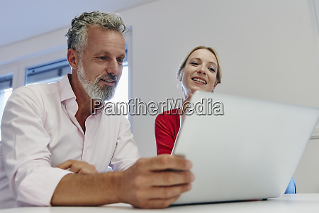 two colleagues working on laptop at