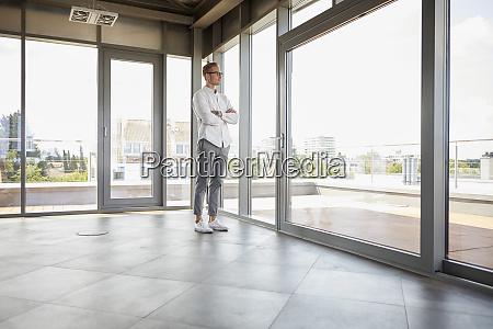 businessman standing in empty room looking