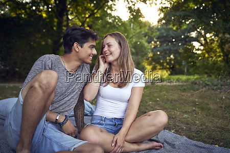 young couple sitting in park sharing