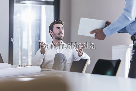 businessman sharing tablet with colleague in