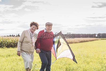 happy senior couple walking with kite