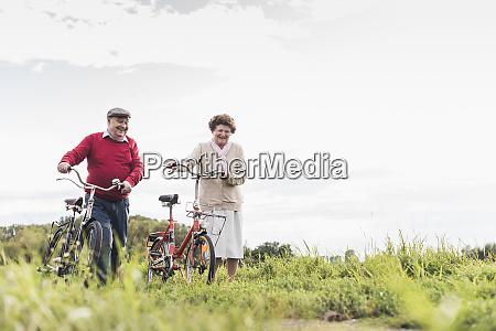 senior couple pushing bicycles in rural