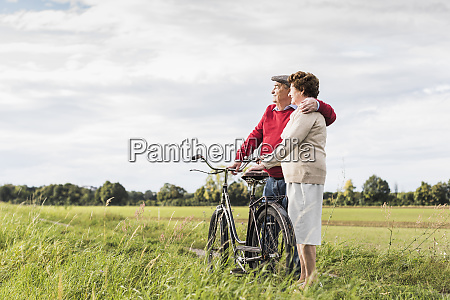 senior couple with bicycles embracing in