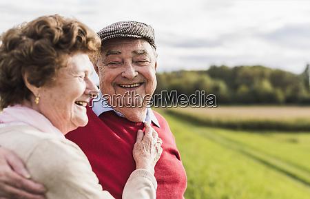 happy senior couple embracing in rural