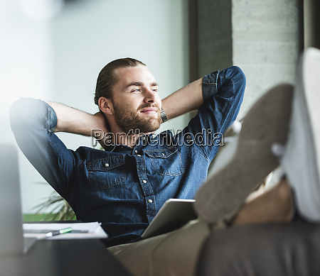 relaxed smiling businessman sitting in office