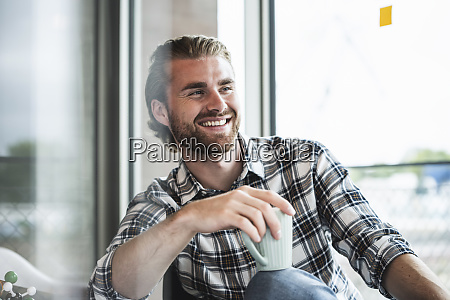 portrait of smiling businessman with cup