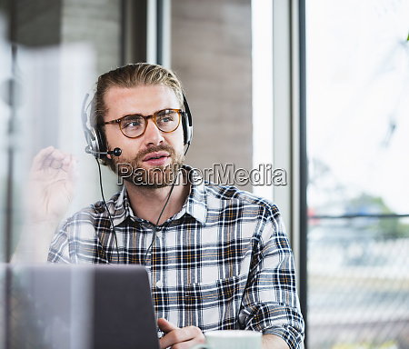 businessman with headset in office using