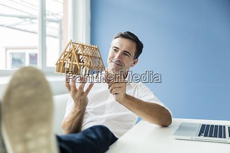 zuversiger geschaeftsmann schaut modellhaus im buero