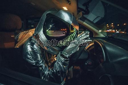 spaceman sitting in car at night