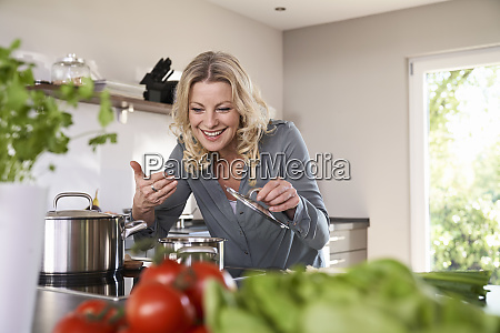 smiling woman cooking in kitchen smelling