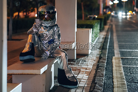 spaceman sitting on bench at a