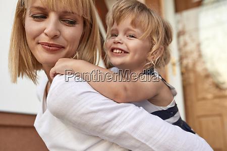 smiling mother carrying her daughter piggyback