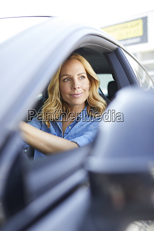 smiling woman driving car looking out