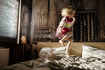 little girl jumping on parents bed
