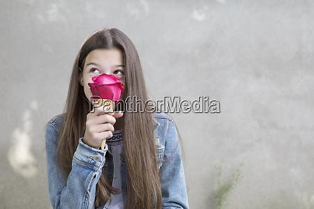 girl smelling pink rose blossom in