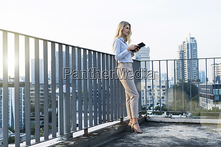 blonde business woman leaning onto handrail