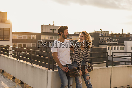 happy young couple relaxing on roof