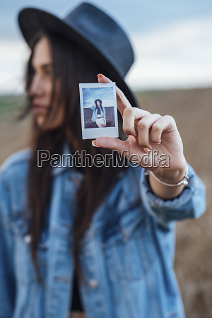 young woman showing instant photo of