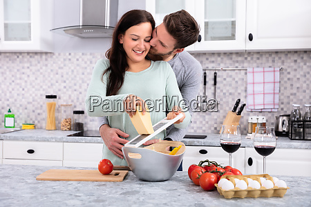 man kissing woman while making delicious