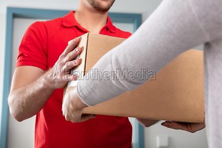 frau die box von lieferung mann