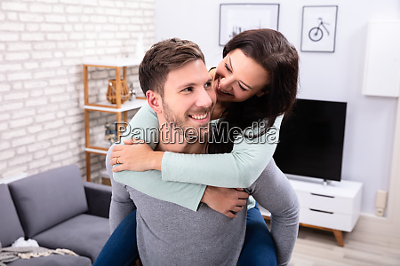 happy man giving piggyback to his