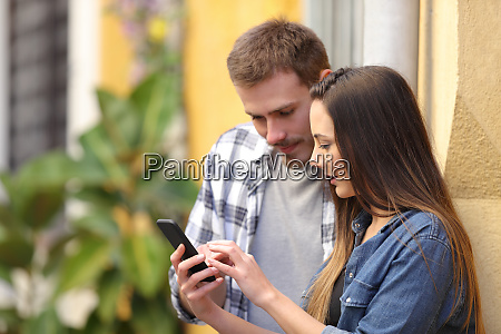 serious couple using smart phone in