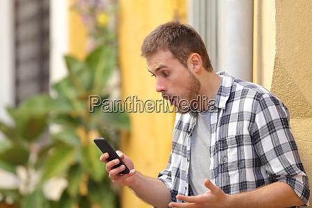 surprised man using smart phone standing