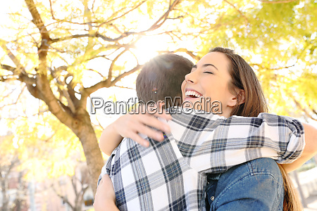 happy couple or friends hugging in