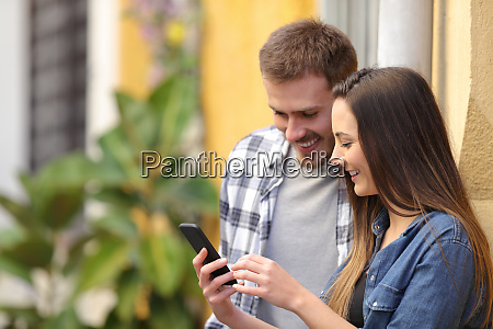 happy couple using smart phone in