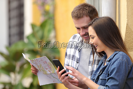 happy tourists checking map and phone