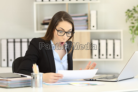 amazed office worker reading sales report