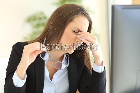 businesswoman suffering eyestrain at office