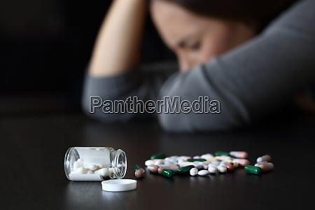 depressive frau neben vielen pillen