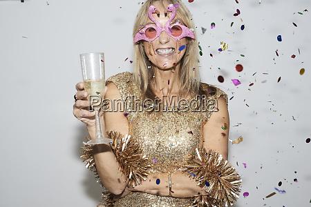 seniorenfrau mit goldenem kleid und flmingo