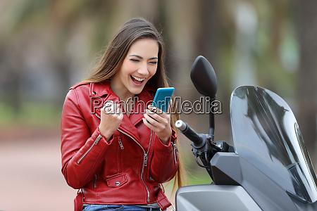 excited motorbiker reading news online