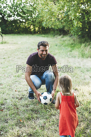 happy father playing football with daughter