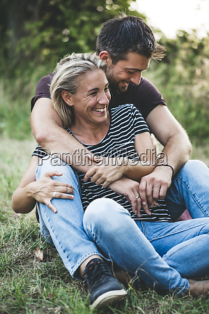 happy couple sitting on a meadow