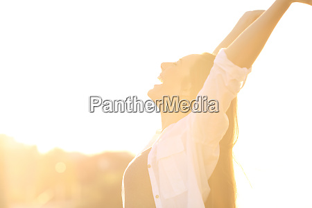 excited woman raising arms at sunset