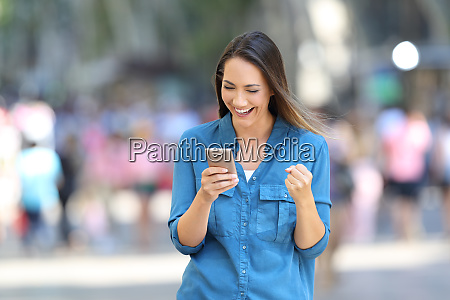 excited woman reading good news online