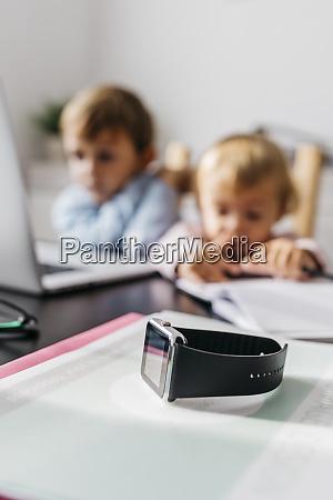 smartwatch auf einem schreibtisch mit kindern