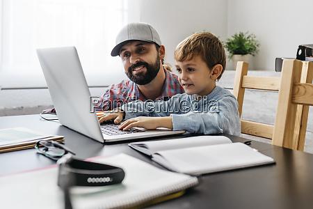 vater und sohn nutzen laptop zusammen